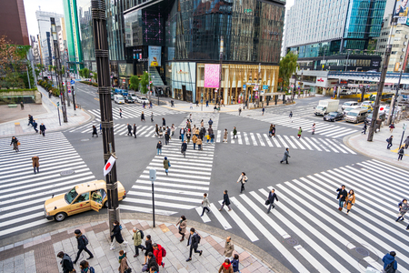 Ginza, Tokyo, Japan - December 27, 2018: Crowd pedestrians people walking on zebra crosswalk at Ginza district in Tokyo, Japan in the morning. Famous busiest shopping for luxury brand name product.