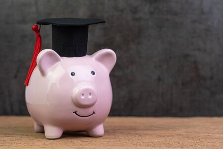 Photo pour Smiling pink piggy bank wearing graduated hat on wooden table with dark black background and copy space, education fund, Scholarships, university cost and expense or saving for student loan concept. - image libre de droit