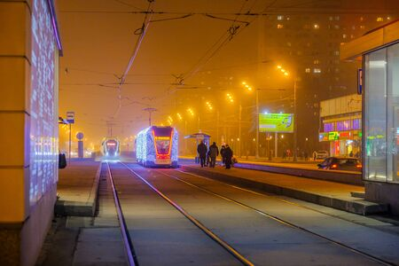Photo pour Moscow.Russia. December 26, 2019. Trams in the fog lit by a network of LEDs arrive at a bus stop with passengers. Environmentally friendly public transport, decorated in honor of the New Year holidays - image libre de droit