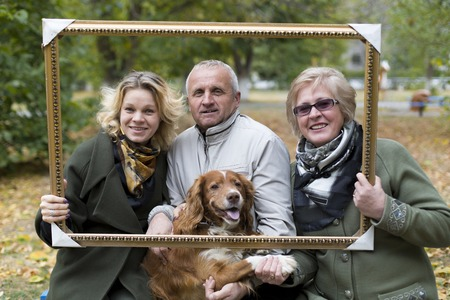 The aged husband with his wife, daughter and dog are photographed in autumn