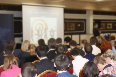 In a huge hall a large number of people are trained, a seminar on new types of business