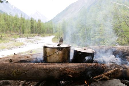 Two pots stand on the fire in the forest. Preparation of food in the trek, two iron pots are heated on an open fire.