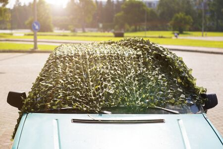 Foto de Car under camouflage net on the street. The car is covered with a protective camouflage net to protect from sunlight and high temperature. - Imagen libre de derechos