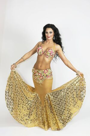 Foto de Oriental dancer in clothes of gold color with black hair and bronze skin gracefully posing a white background. A brunette woman in a dance suit on a white background. - Imagen libre de derechos