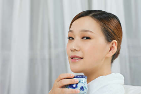 Photo pour A young woman wearing a bathrobe drinking tea - image libre de droit