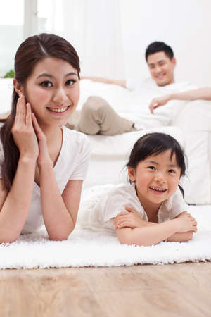 Photo pour Young family sitting in couch - image libre de droit