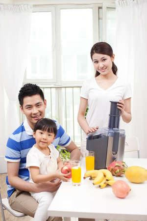 Photo pour Happy family making juice with electric juicer - image libre de droit