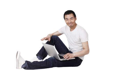 Photo pour Cheerful businessman using a laptop on carpet - image libre de droit