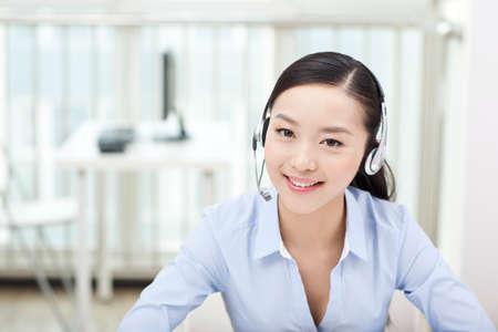 Photo pour Female office worker wearing headset,portrait - image libre de droit