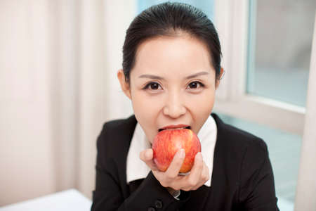 Photo pour Businesswoman in her office eating an red apple - image libre de droit
