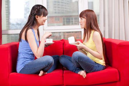 Photo pour Portrait of two female friends drinking coffee at home - image libre de droit