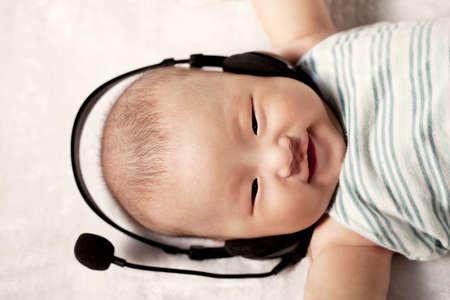Photo pour A baby wearing a headset - image libre de droit