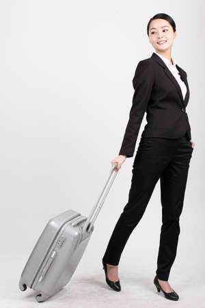 A business lady in a suit pulls a suitcase high quality photo