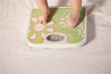 Photo pour Baby standing on the weight scale high quality photo - image libre de droit