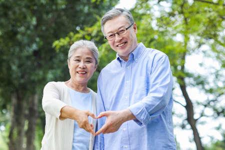 Photo pour Portrait of happy old couple with Heart gesture - image libre de droit