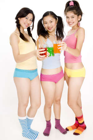 Three young women drinking fizzy drinks