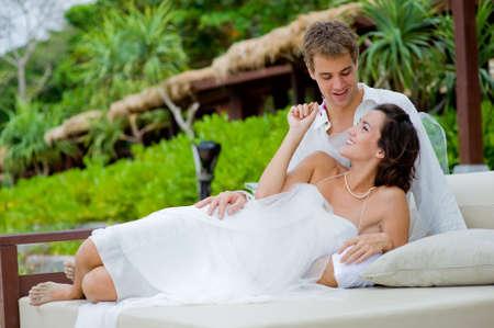 Foto de A young bride and groom lying together in an outdoor setting by beach - Imagen libre de derechos