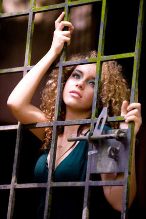 Photo for A pretty young woman behind bars - Royalty Free Image