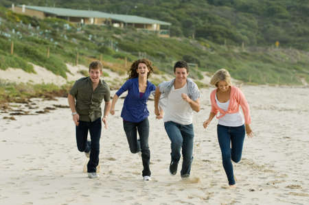 Four friends running along a sandy beach in autumn