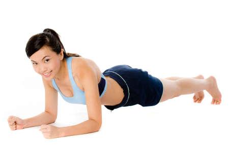 Foto de A young attractive Asian woman in sportswear doing a plank pose - Imagen libre de derechos
