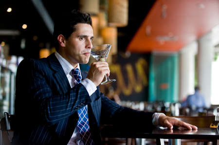 A young businessman sitting in a bar with a martini