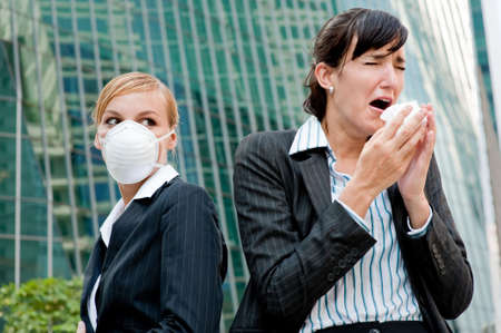 A businesswoman sneezing as another with health mask on stares at her