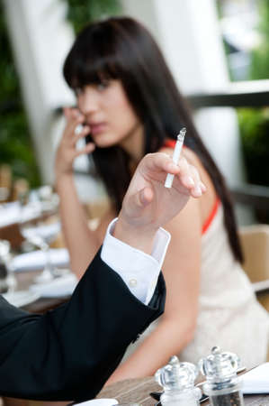 A young and attractive woman covers her nose to avoid the smoke from a cigarette at an outdoor dining area