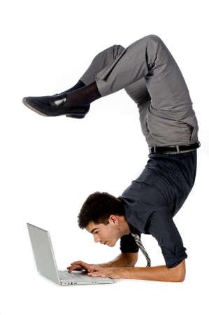 Foto de An attractive athletic businessman doing a handstand while using his laptop against white background - Imagen libre de derechos