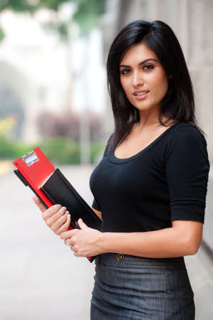 A beautiful young businesswoman standing outside holding files and notebook