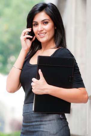 A young attractive Asian businesswoman standing outside with mobile phone