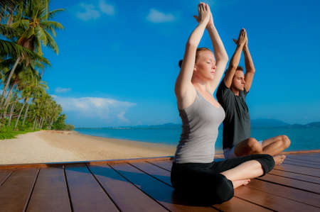 Photo for An attractive young woman and man doing yoga on a jetty with the blue ocean and another island behind them - Royalty Free Image