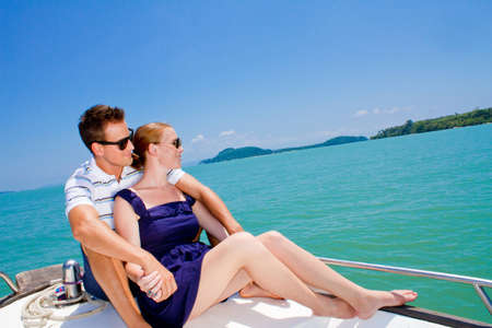 Photo for An attractive young couple relaxing outdoors together on a boat - Royalty Free Image