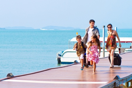 Foto de A family of 4 arriving at the resort with their luggages. - Imagen libre de derechos