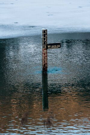 Photo pour water depth measurement tool in mountains partially iced lake in Tyrol (Austria) - image libre de droit