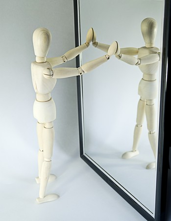 Closeup of wooden mannequin looking in full length mirror, white studio background.