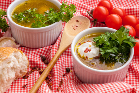 Homemade sausage soup with sour cream and parsley in white bowls