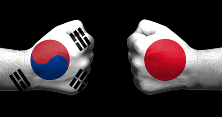 Flags of Japan and South Korea painted on two clenched fists facing each other on black background/