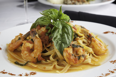 A white plate holds linguine with shrimp in a fra diavolo sauce, topped with fresh basil. Paprika is sprinkled on the sides of the plate for decoration. Everything sits on a white tablecloth.