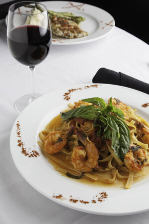 A white plate holds linguine with shrimp in a fra diavolo sauce, topped with fresh basil. Paprika is sprinkled on the sides of the plate for decoration.  A glass of red wine and a black napkin roll of utensils surrounds the plate.  Another dish can be see