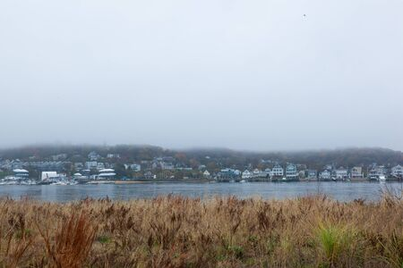 Photo pour A view of the Atlantic Highlands over the Shrewsbury River on a foggy autumn day. Photo taken from Sandy Hook. The Twin Lights lighthouses are barely visable through the fog. - image libre de droit