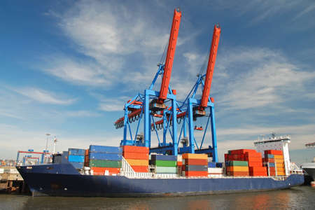 blue container ship unloading freight with two cranes