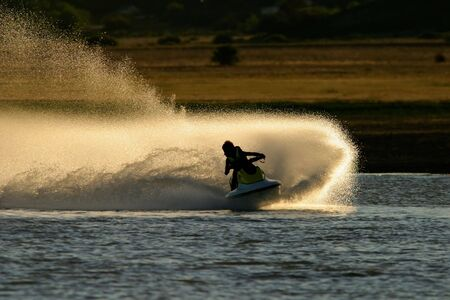 Photo pour Backlit jet ski with water spray, late afternoon - image libre de droit