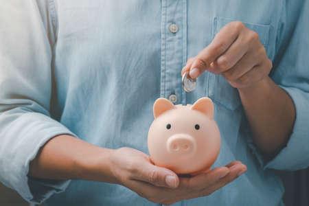 Photo pour female hands puts a coin in a pink piggy bank. The concept of saving money. - image libre de droit