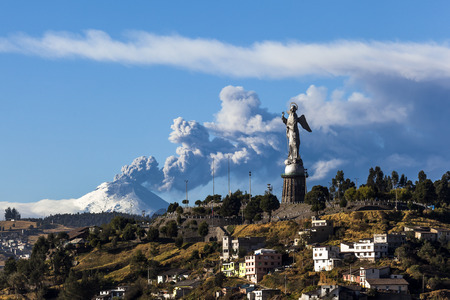 Cotopaxi volcano eruption and Panecillo's Madona seen from Quito, Ecuador