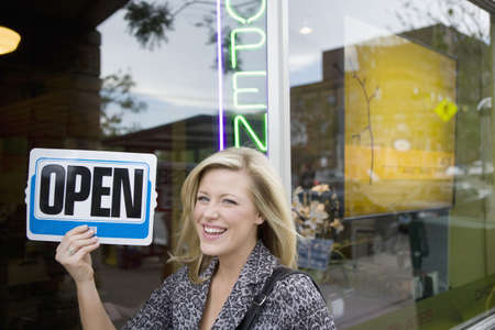 Photo for A happy owner holding up an Open sign in front of her new business - Royalty Free Image
