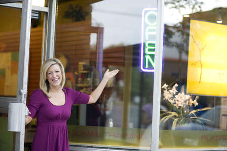 A happy business owner opening her shop door
