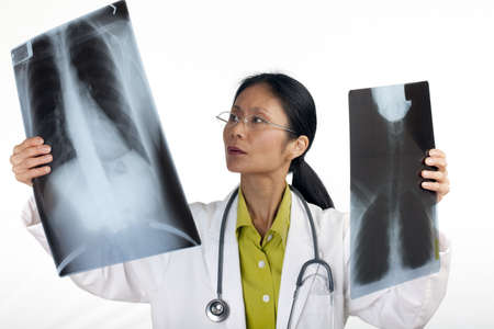 Asian female doctor reviews the results of a chest x-ray. Horizontal shot. Isolated on white.