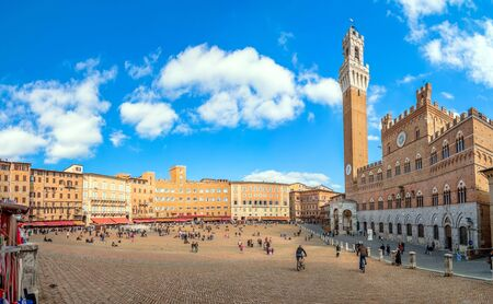 SIENA ITALY  October 26 2014: tourists enjoy Piazza del Campo square in Siena Italy. The historic centre of Siena has been declared by UNESCO a World Heritage Site.