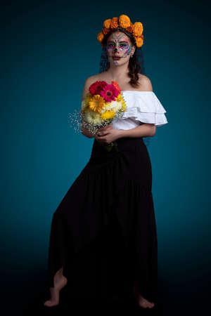 Foto de Latin woman with Catrina makeup, black dress and a bouquet of flowers in her hands - Imagen libre de derechos