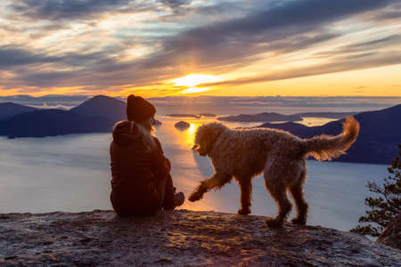 Foto per Adventurous Girl Hiking on top of a Mountain with a dog during a colorful sunset. Taken on Tunnel Bluffs Hike, near Vancouver and Squamish, British Columbia, Canada. - Immagine Royalty Free
